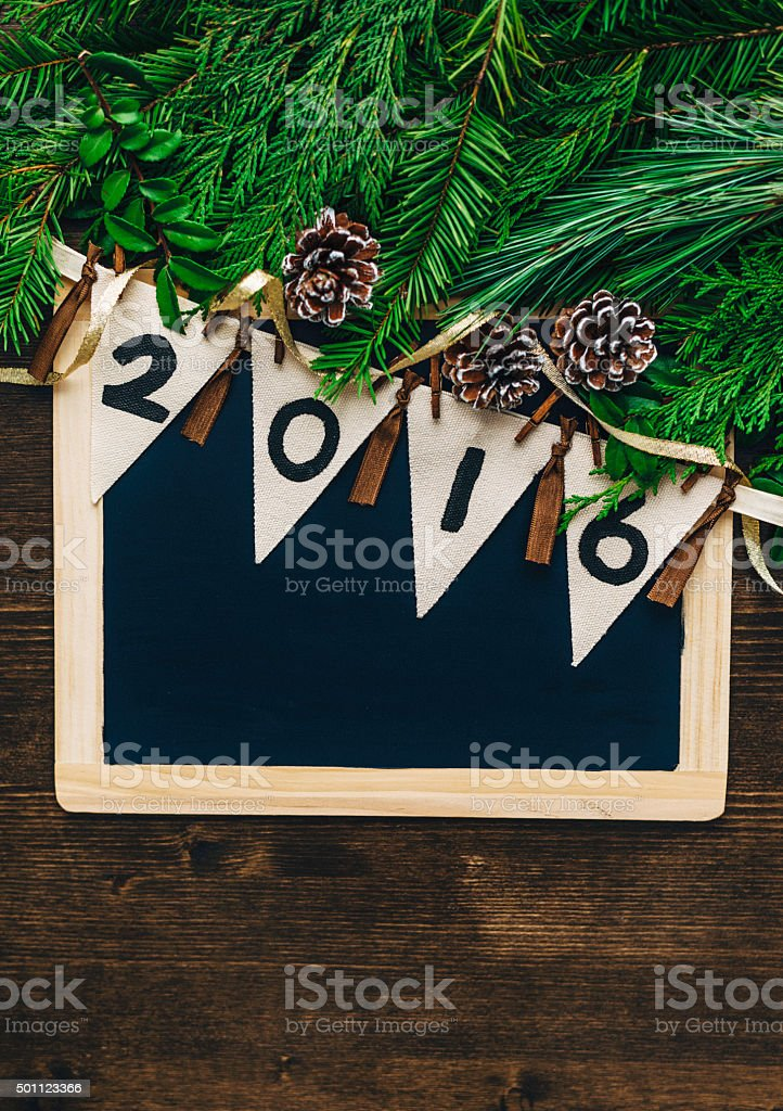 New Year 2016 banner on chalkboard with assorted Christmas foliage stock photo