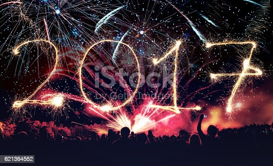 istock new year 2017 banner with  fireworks and cheering crowd 621364552