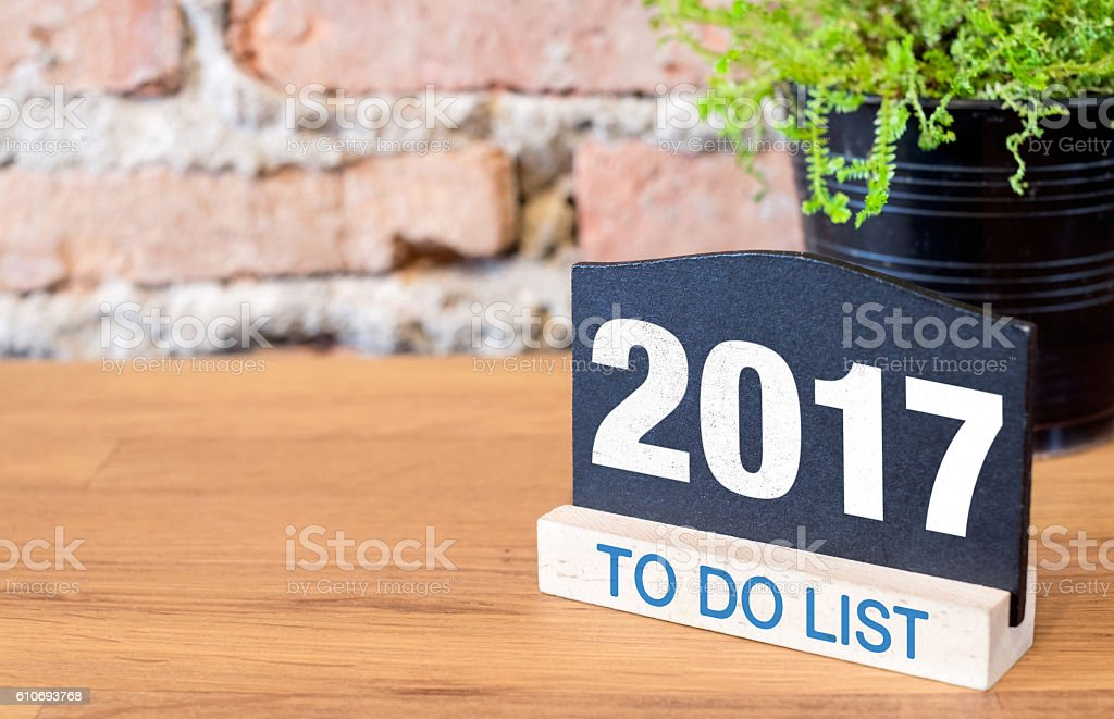 New year 2017 on blackboard and green plant on table stock photo