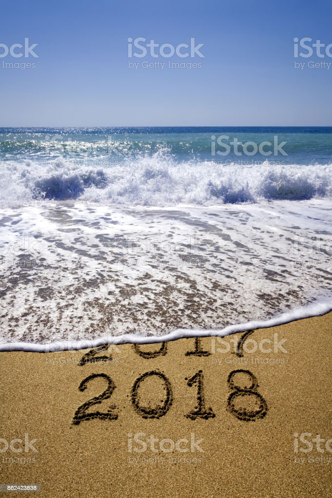 New year 2018 and 2017 on sandy beach with waves stock photo
