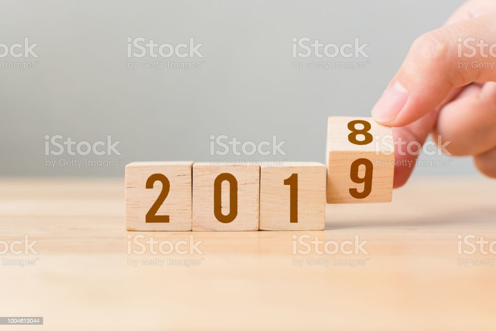 New year 2018 change to 2019 concept. Hand flip over wood cube block stock photo