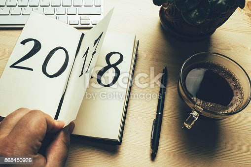 istock New Year 2018 is coming concept. Hand flips notepad sheet on wooden table. 2017 is turning, 2018 is opening 868450926