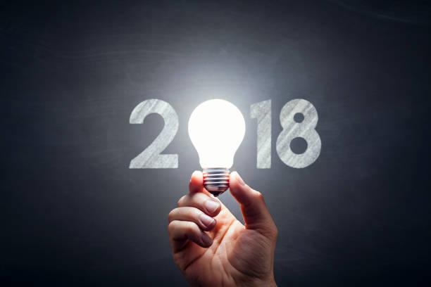 neue jahr 2018 - glühbirne hand idee blackboard - ideen für silvester stock-fotos und bilder
