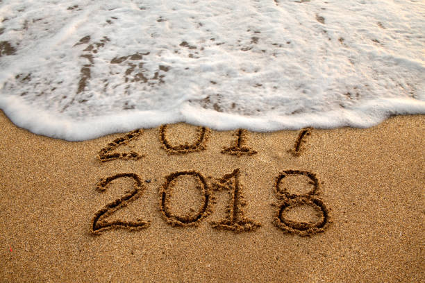 New year 2018 New year 2018 and old year 2017 written on sandy beach with waves 2017 stock pictures, royalty-free photos & images