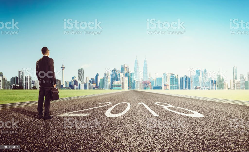 New year 2018 ,young businessman looking on city skyline background . Determined to start concept . stock photo