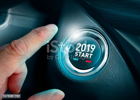 Hand pushing New Year 2019 button in the car