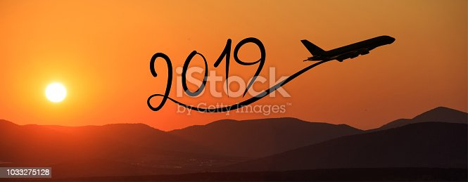 istock New year 2019 by flying airplane on the air at sunrise, banner 1033275128