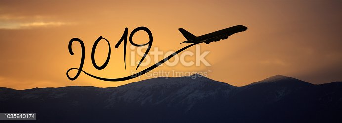 istock New year 2019 by flying airplane on the air at sunrise, banner 1035640174