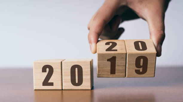 New year 2019 change to 2020 concept, hand change wooden cubes stock photo