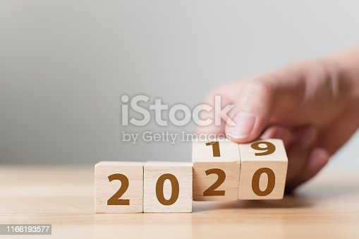 945046208 istock photo New year 2019 change to 2020 concept. Hand flip over wood cube block 1166193577