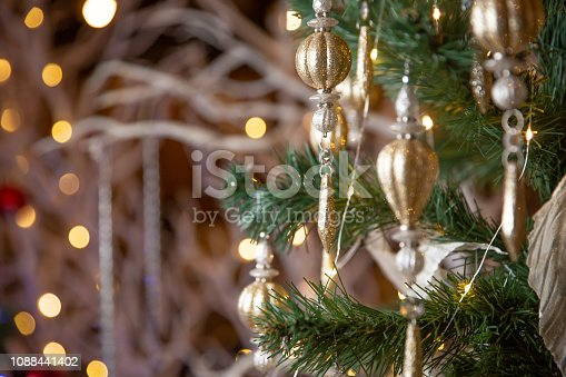 istock New Year 2019. Christmas beautiful lights bokeh on gold warm background. Defocused Lights on a Tree Background. Christmas tree toys. 1088441402