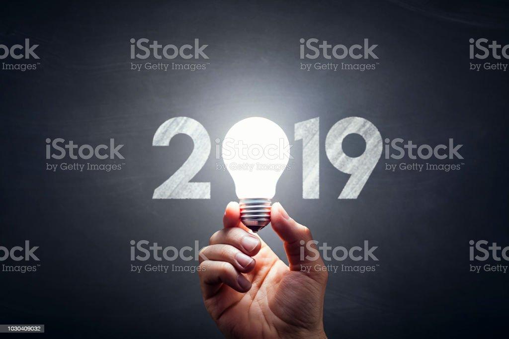 New Year 2019 - Light Bulb Hand Idea Blackboard stock photo