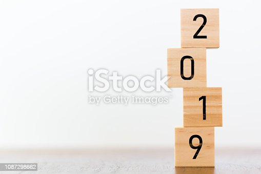 1066508880 istock photo New year 2019 on wooden cubes on table with copy space for text 1087298662