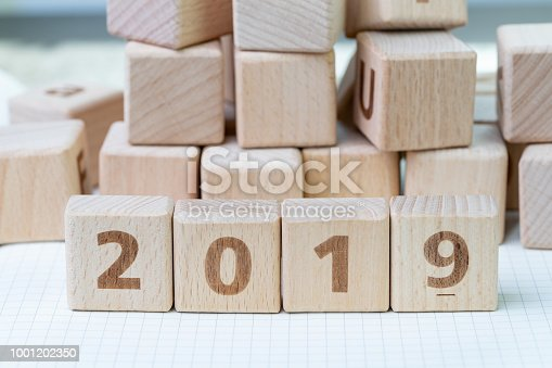 1186985932 istock photo New year 2019, review or resolution concept, cube wooden block with alphabet building the numbers 2019 on grid line notebooks with other random block in the background 1001202350