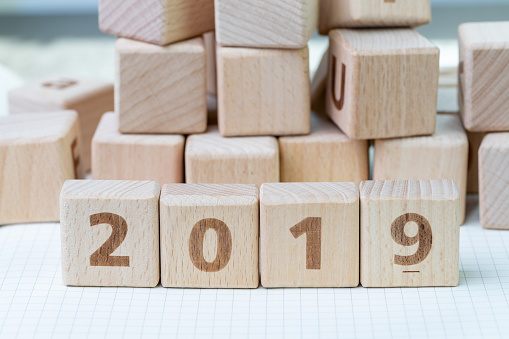1163501702 istock photo New year 2019, review or resolution concept, cube wooden block with alphabet building the numbers 2019 on grid line notebooks with other random block in the background 1001202350