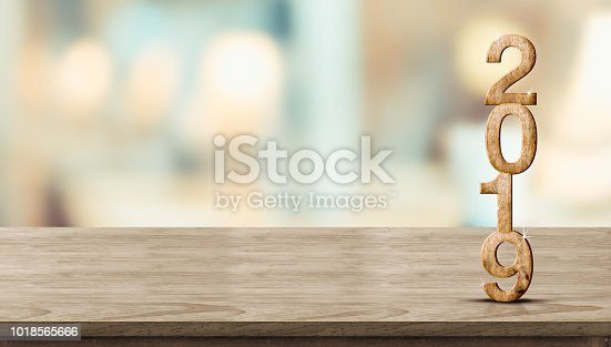 istock New year 2019 wood number (3d rendering) on wooden table at blur abstract bokeh light background,Mock up banner space for display or montage of product,holiday celebration greeting card. 1018565666