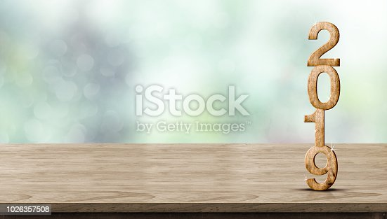 istock New year 2019 wood number (3d rendering) on wooden table at blur abstract green bokeh background,Mock up banner space for display or montage of product,holiday celebration greeting card. 1026357508