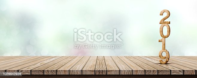 istock New year 2019 wood number (3d rendering) on wooden table at blur abstract green bokeh background,Mock up banner space for display or montage of product,holiday celebration greeting card. 1029642934