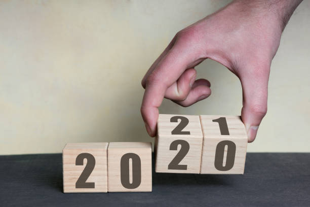 New year 2020 change to 2021 concept, hand change wooden cubes stock photo