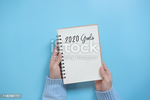 New Year 2020 goals list with notebook on blue background, flat lay style. Planning concept.