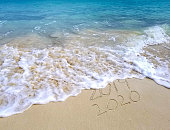 frothy ocean surf and sand for New Year 2020 holiday
