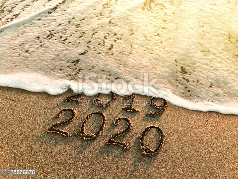 New year 2020 and old year 2019 written on sandy beach with waves