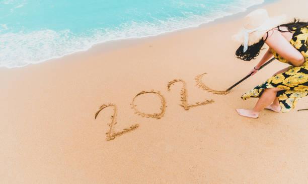 2020 Neujahr. 2020 Frau geschrieben auf Sandstrand mit Wellenschaum am Strand. Frohes neues Jahr. Tropische Feier. Neujahrskonzept. – Foto