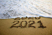 istock New year 2021 and 2020 on sandy beach with waves 1257464394