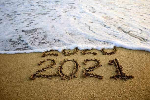 New year 2021 and 2020 on sandy beach with waves New year 2021 and old year 2020 on sandy beach with waves new years day stock pictures, royalty-free photos & images