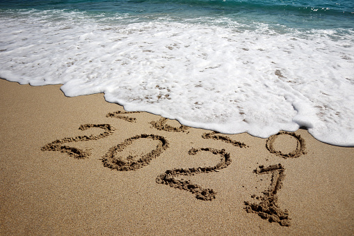 New year 2021 and old year 2020 written on sandy beach with waves