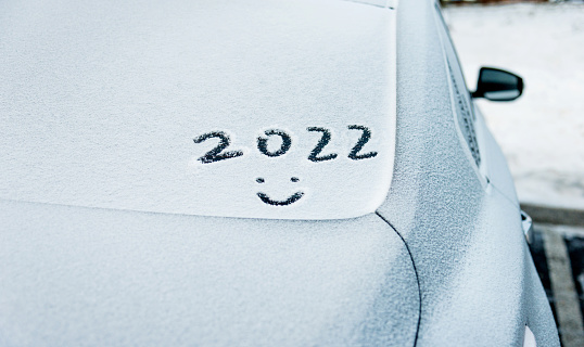 New year 2022 and smiling face written on the rear windshield with snow