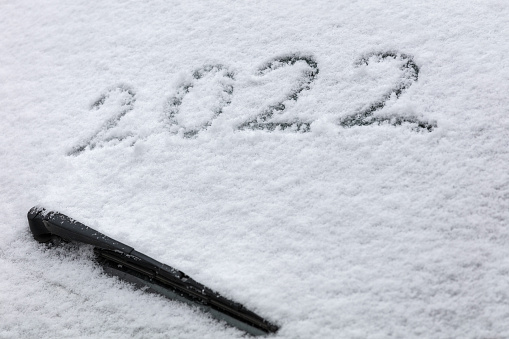 The new year 2022 written on a car windshield