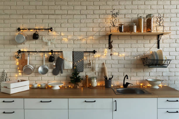 New Year and Christmas 2019. Festive kitchen in Christmas decorations. Candles, spruce branches, wooden stands, table laying. stock photo