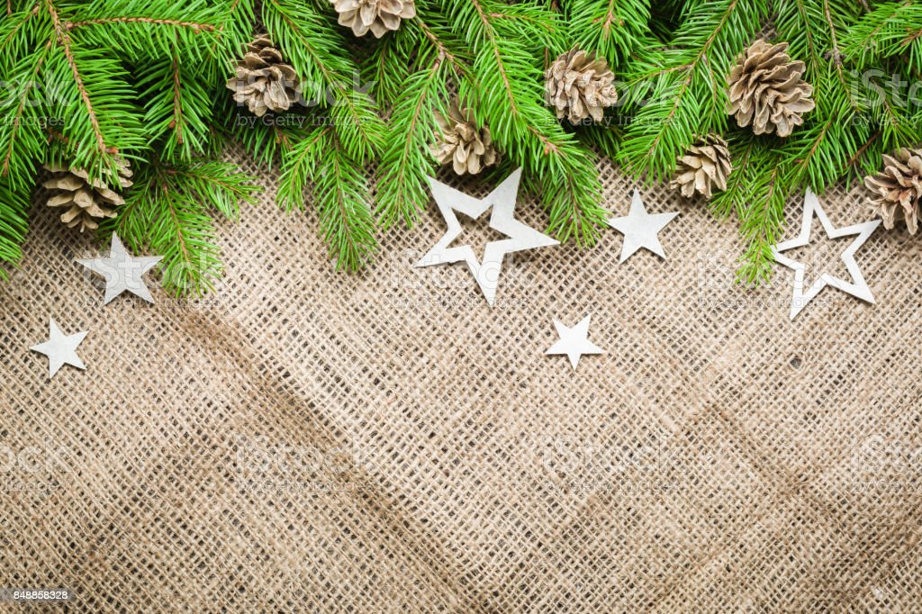 New Year and Christmas background on an old background of sackcloth. View from above. Christmas tree branches and snow, gifts and decorations. stock photo