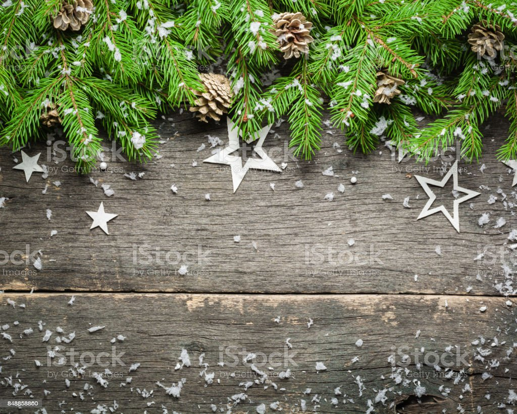 New Year and Christmas background on an old gray wooden background. View from above. Christmas tree branches and snow, gifts and decorations. stock photo