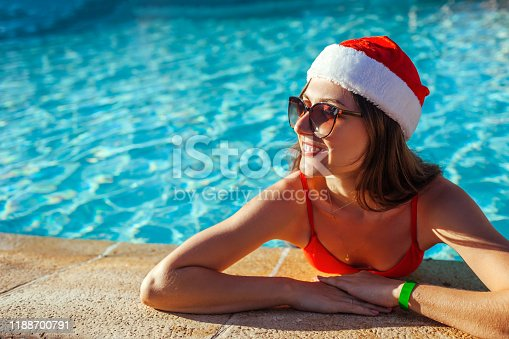 New Year and Christmas celebration. Woman in Santa's hat and bikini relaxing in swimming pool. Tropical winter vacation
