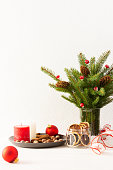 Candles with dried slices of citrus fruits, hazelnuts with cinnamon, fir tree branches and cones in a vase on white wall background, new year and christmas concept