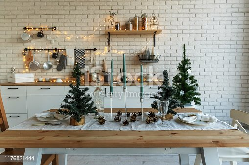 New Year and Christmas. Festive kitchen in Christmas decorations. Candles, spruce branches, wooden stands, table laying