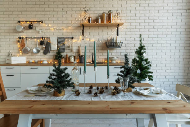 new year and christmas. festive kitchen in christmas decorations. candles, spruce branches, wooden stands, table laying. - christmas table foto e immagini stock