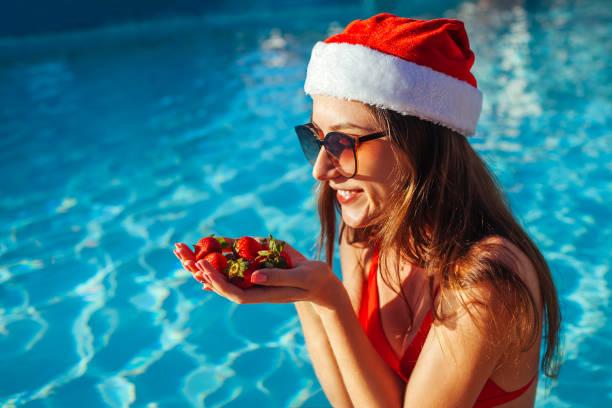neujahr und weihnachtsfeiertag. frau in santa s hut und bikini essen erdbeeren im schwimmbad. tropischer urlaub - weihnachtsmannhüte aus erdbeeren stock-fotos und bilder