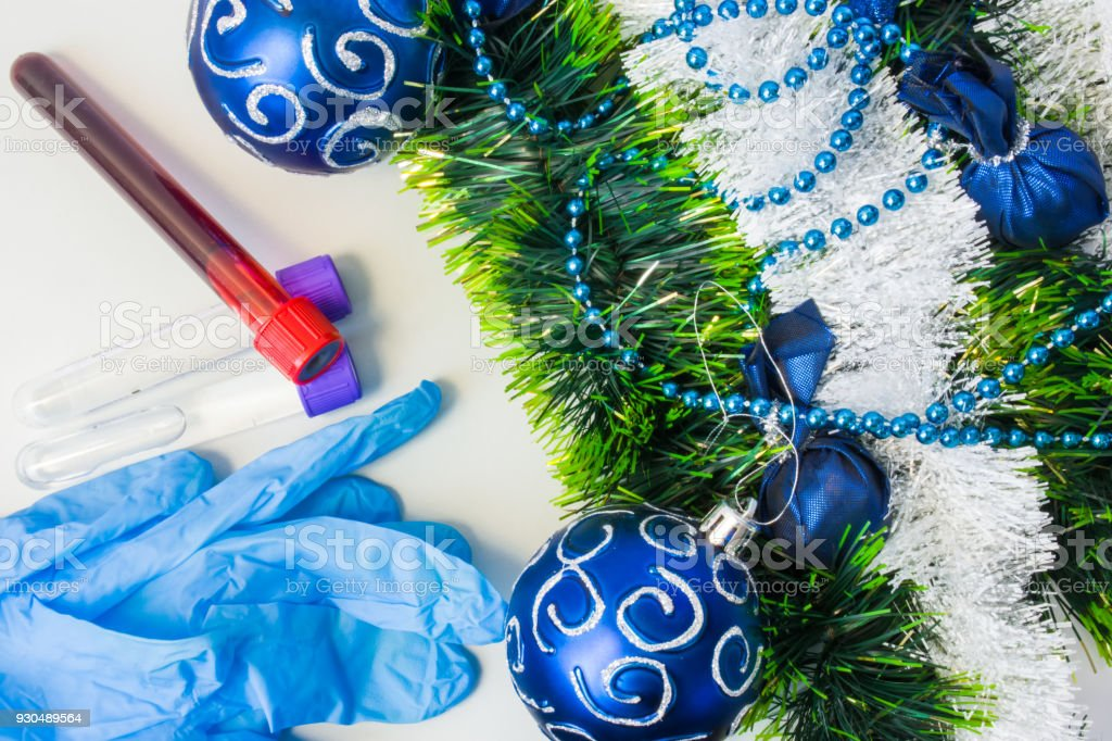 New Year and Christmas in medical, clinical or scientific laboratory. Protective gloves and laboratory test tubes with blood samples or other biological fluids lie near Christmas decorations and balls stock photo