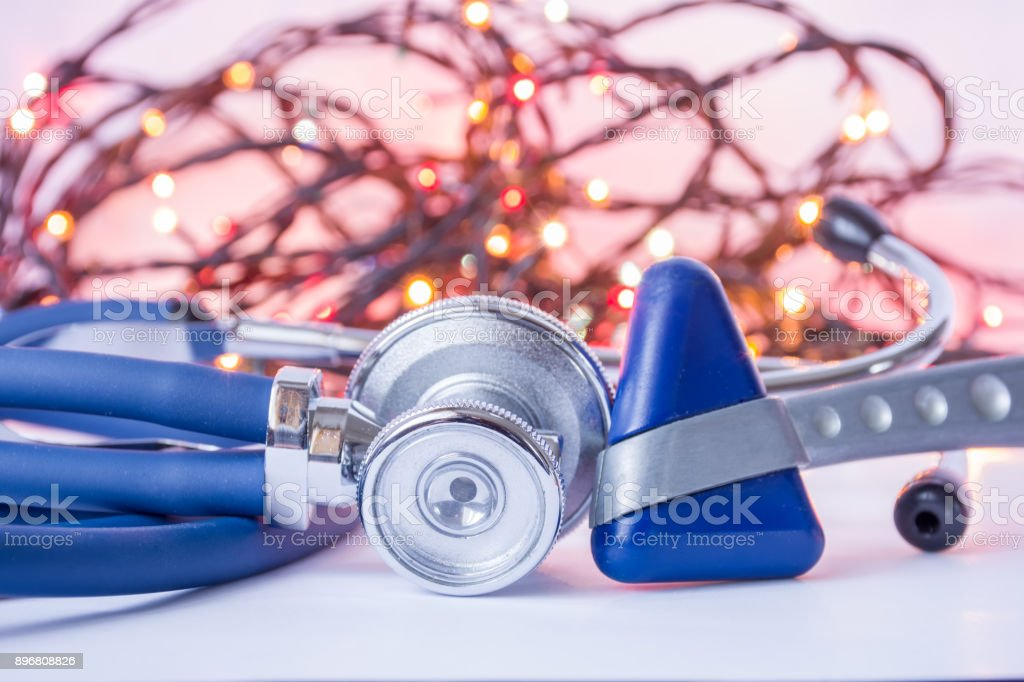 New Year and Christmas in neurology, internal medicine, general practice. Medical stethoscope and neurological reflex hummer in foreground with blurred lights bulbs Christmas garlands in background stock photo