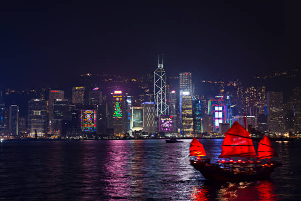 New year and Christmas skyline shines landmark at Victoria harbour night scene with Chinese red sail junk boat Hong Kong - December 9, 2017. New year and Christmas skyline shines landmark at Victoria harbour night scene with fog in Hong Kong winter festival. Hong Kong  has one of the world's most festive Christmases and New year count down bank of china stock pictures, royalty-free photos & images