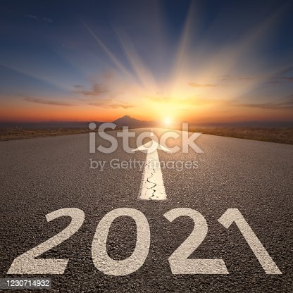 Driving on idyllic open road against the setting sun forward to upcoming 2021 new year. Concept for success and future.