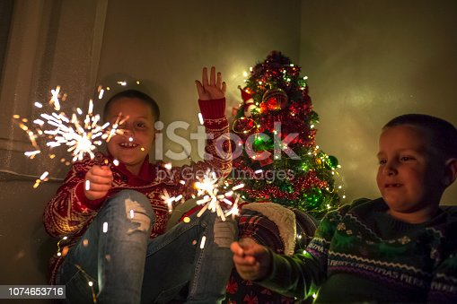 Two boys having fun, holding sparkles on New Years eve
