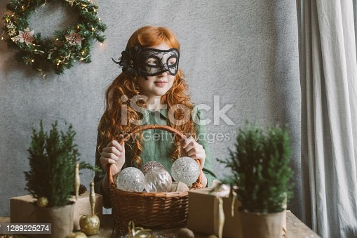 Redhead girl in a carnival mask holds a basket with Christmas decorations.