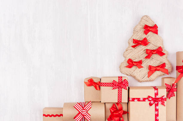 new year background various handmade kraft paper present boxes with bright red ribbons and bows