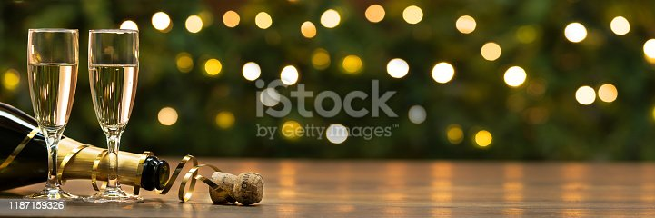 New Year toast champagne, lights bokeh background