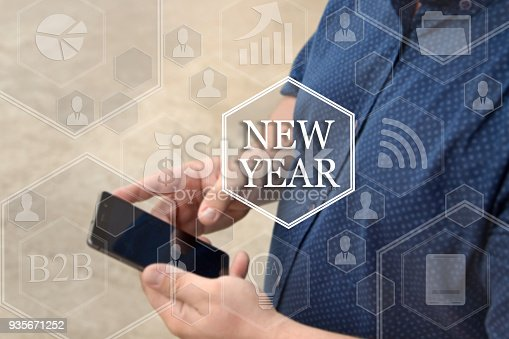 istock New Year, button on the touch screen with a blur background of the businessman with the phone. The concept of innovation, business vision , webinar. 935671252
