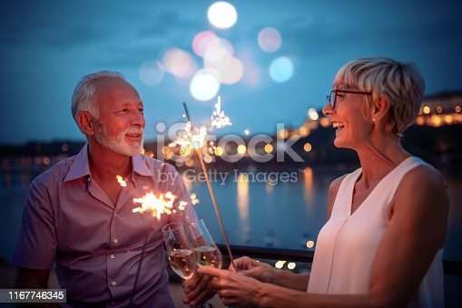 Senior couple having nice time on rooftop terrace.